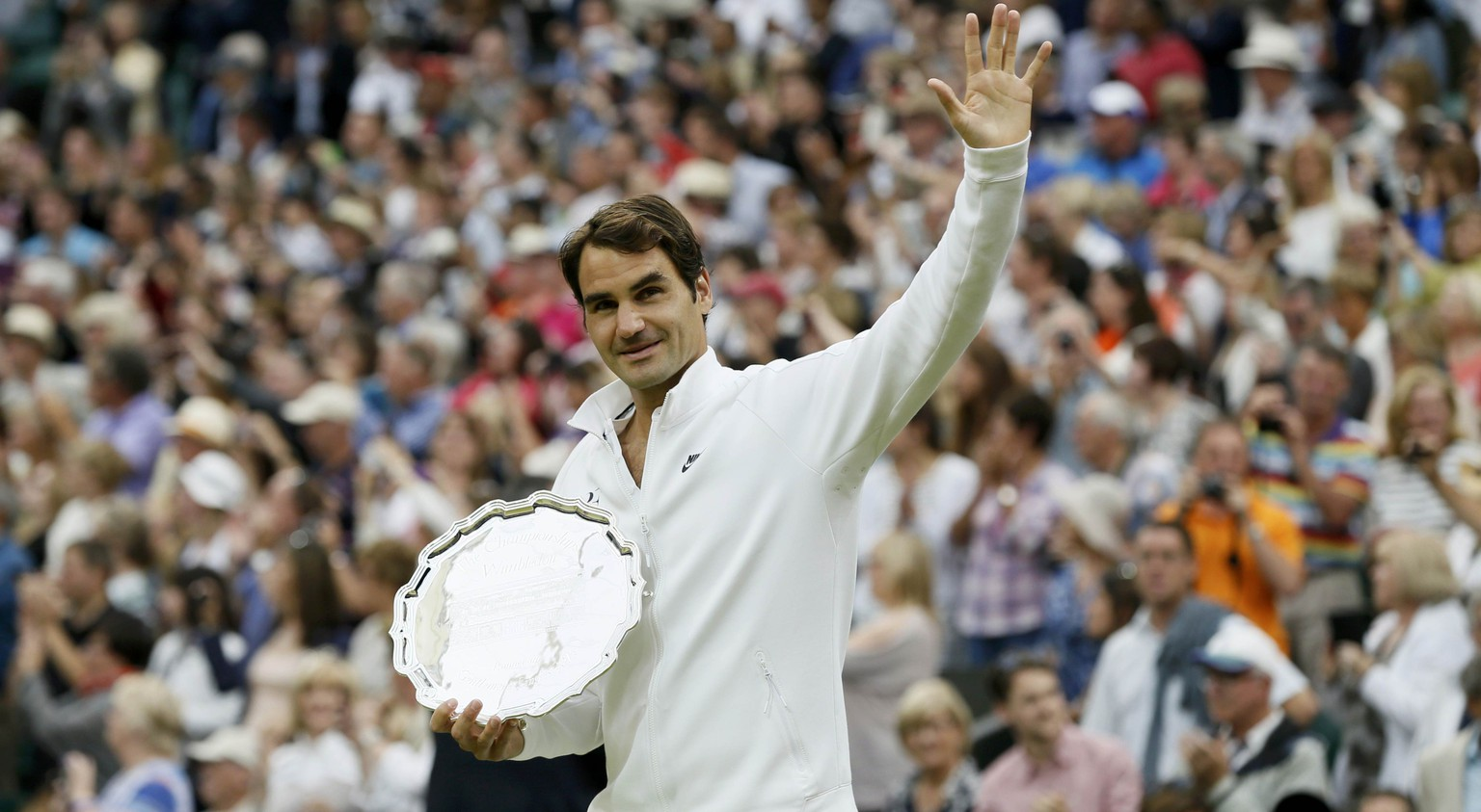 Roger Federer of Switzerland waves with the runner up trophy after losing his Men's Singles Final match against Novak Djokovic of Serbia at the Wimbledon Tennis Championships in London, July 12, 2015.                                                        REUTERS/Stefan Wermuth